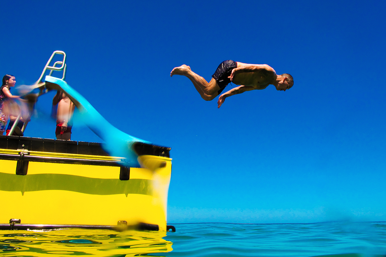 Man leaping off beach pontoon