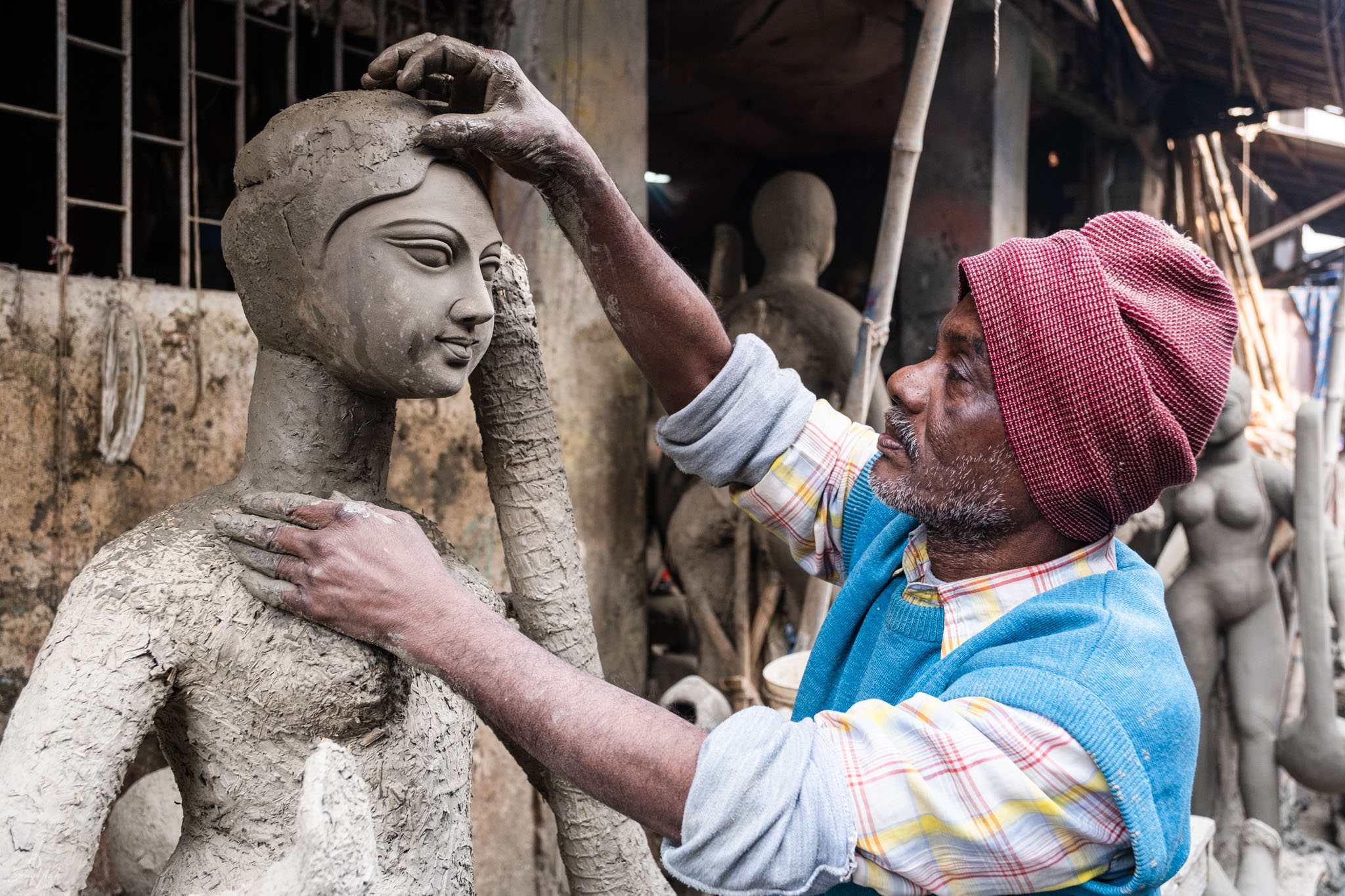 Clay sculptor working on effigy of Saraswati