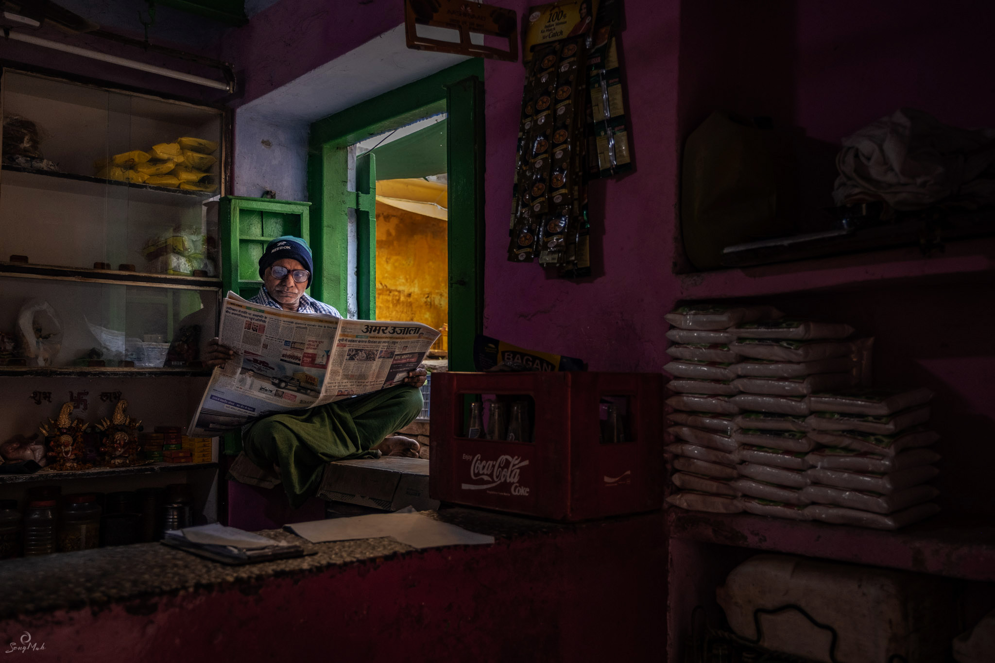 Interior scene of man reading newspaper in shop