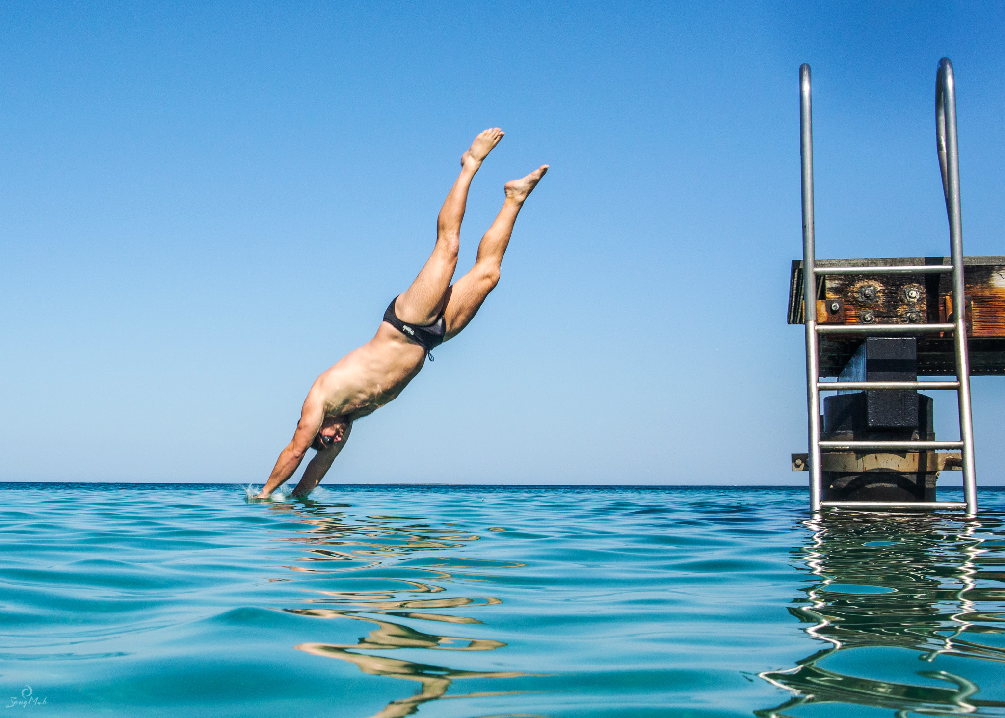 Man diving off jetty into the sea