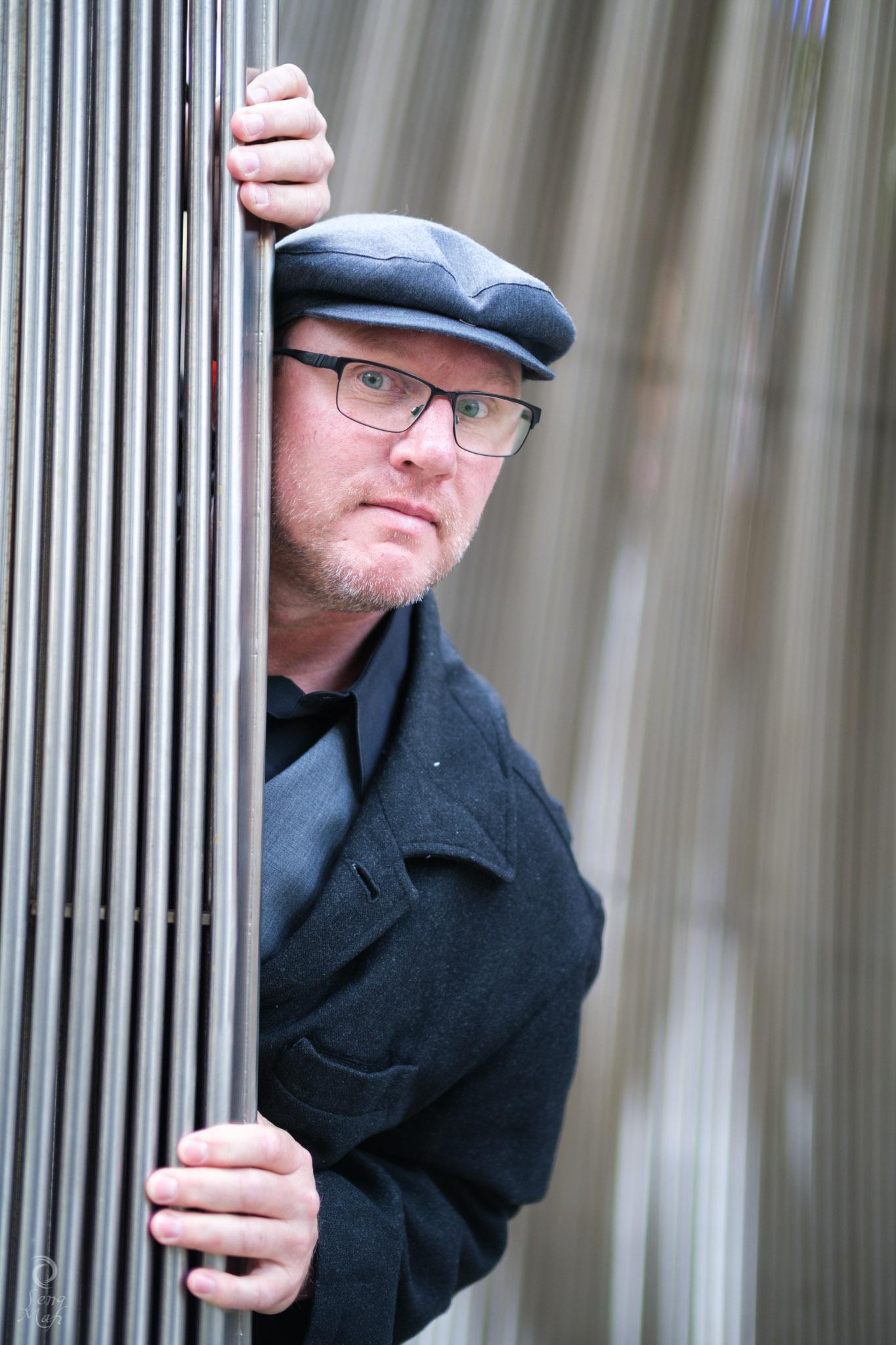Man peeking from behind sculpture