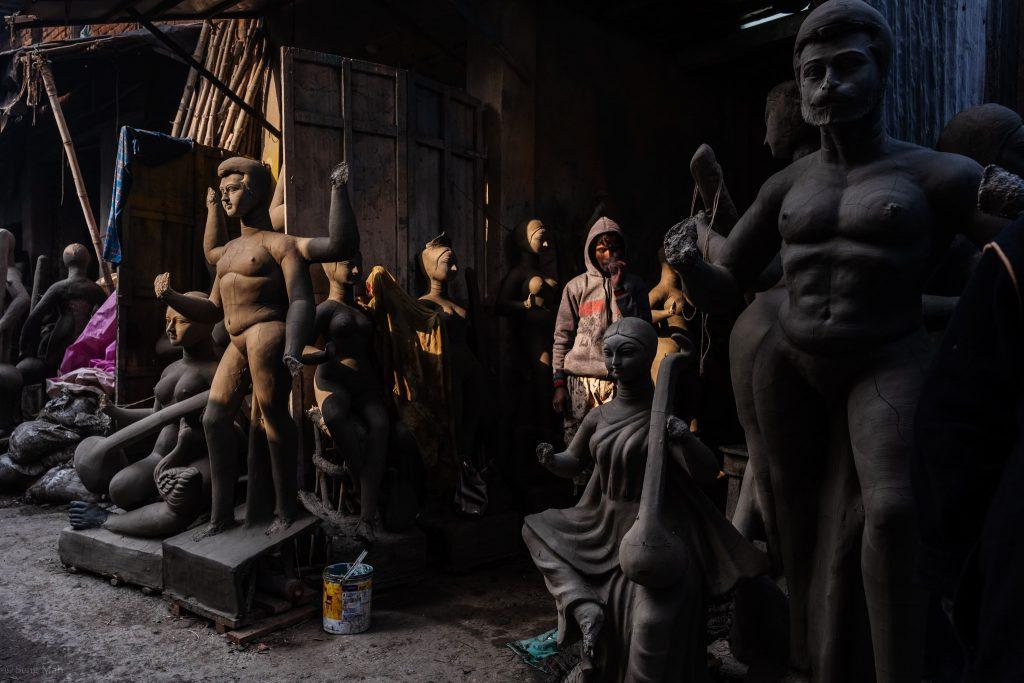 A man stands in the shadows of a clay effigy shop in Kumartolli, Kolkata