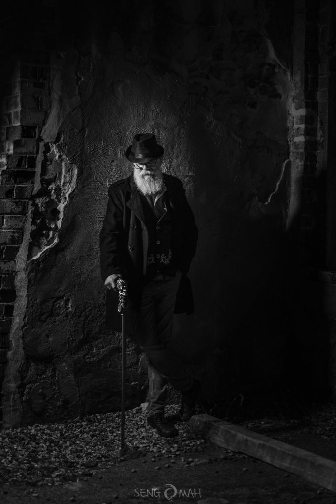 A moody black and white picture of a bearded man dressed in a hat and jacket, holding a walking stick and standing next to an old wall.