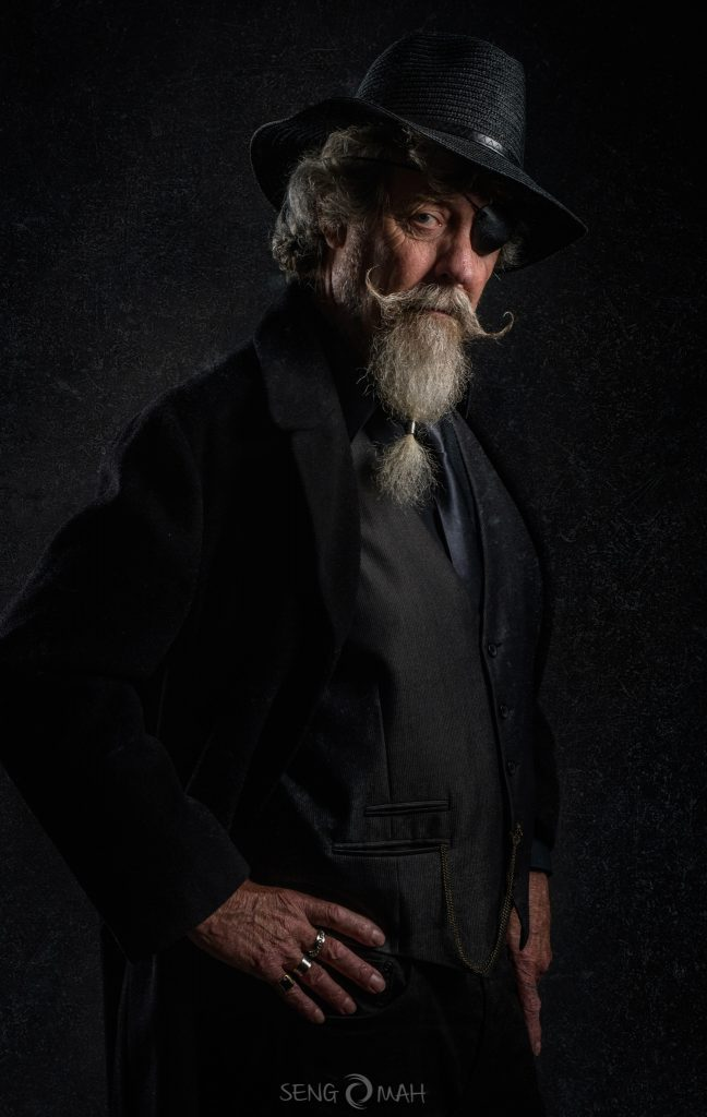 A bearded man dressed in black period hat and jacket, with an eye patch.