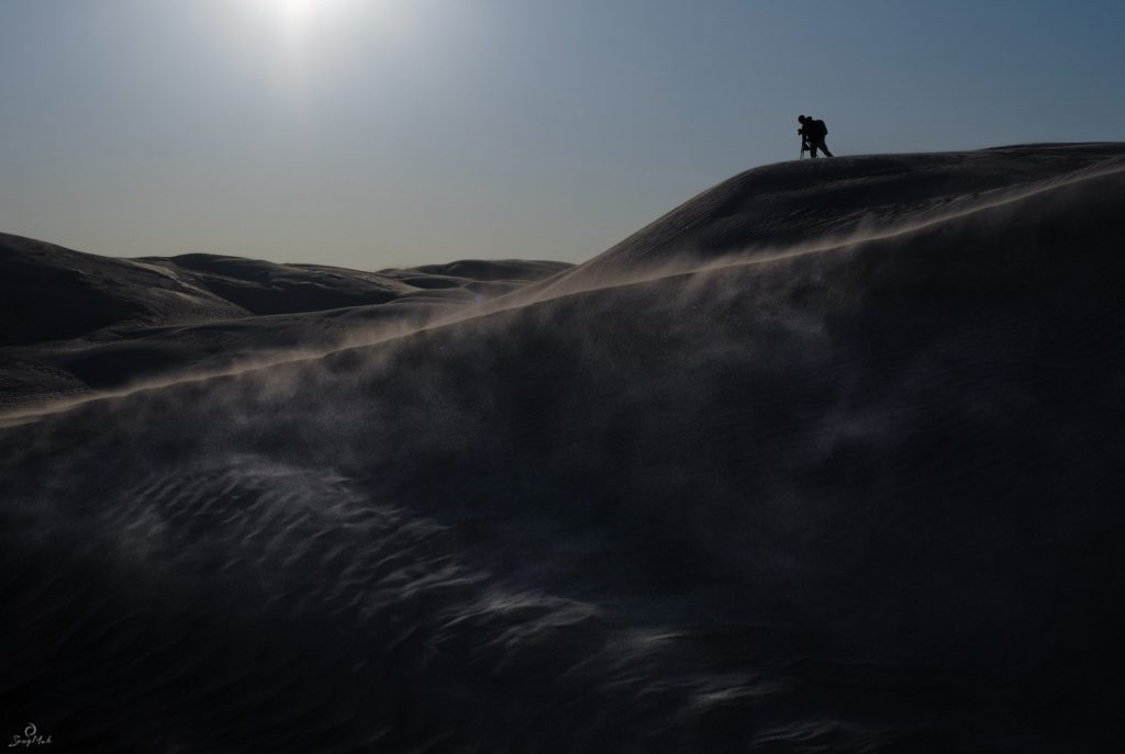 A lone photographer stands on top of a sand dune, surrounded by sand drifting in the wind.