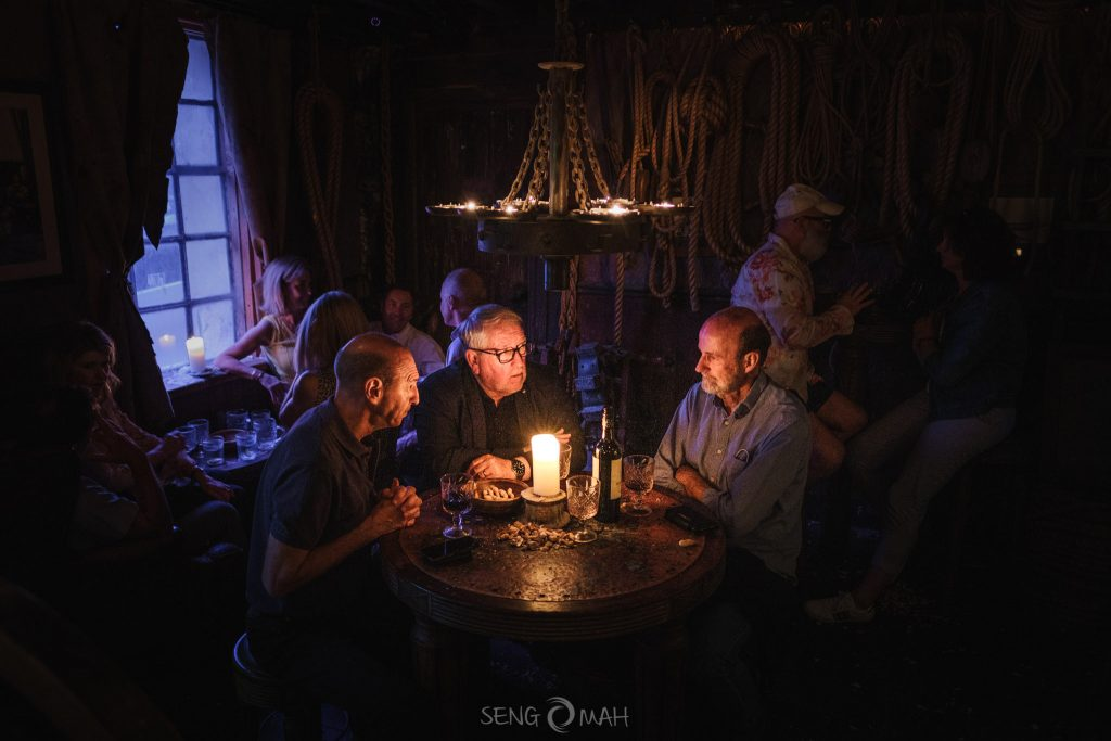 An interior scene taken inside a stylised bar with three men sitting around a table in deep conversation.