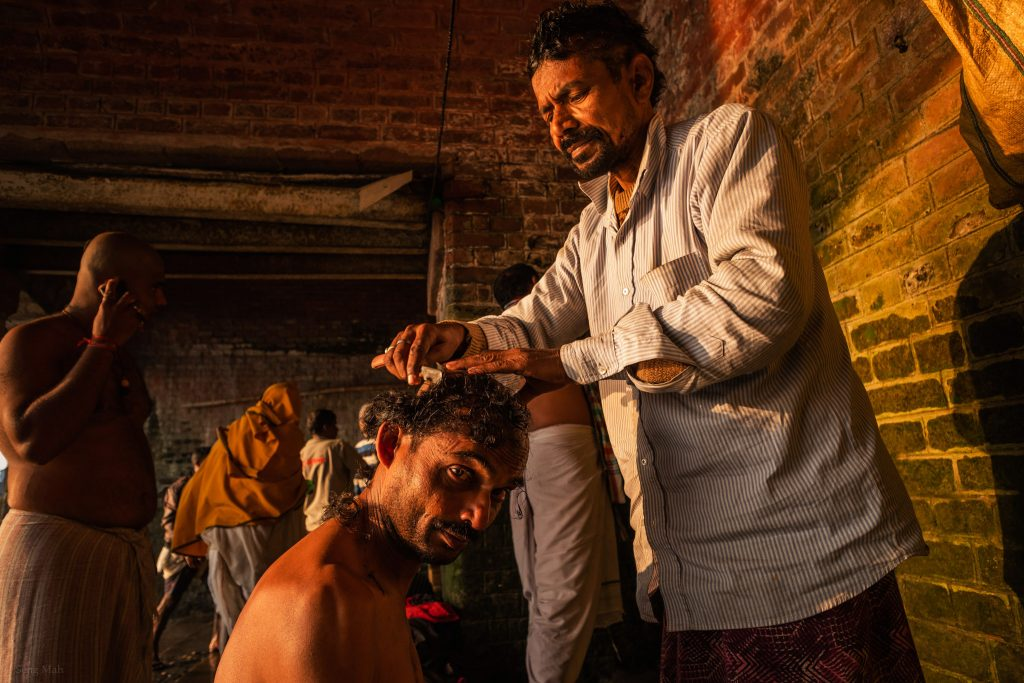 A barber shaves a man's head under the Hooghly Bridge in Kolkata.