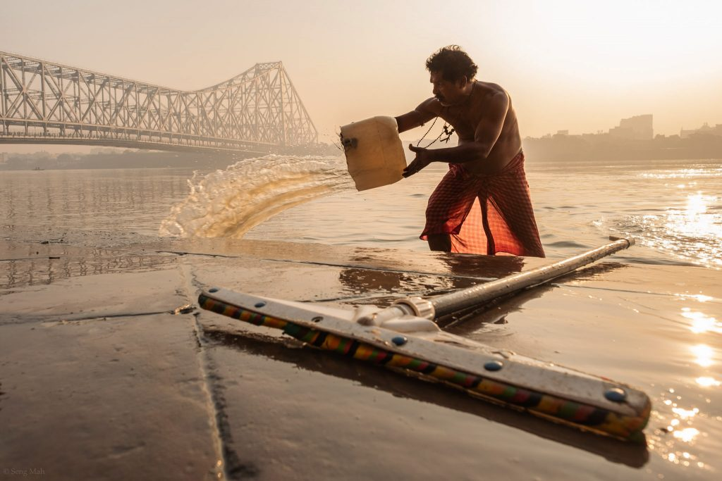 A man splashes water on the ghats of the Hooghly River at sunrise in Kolkata.