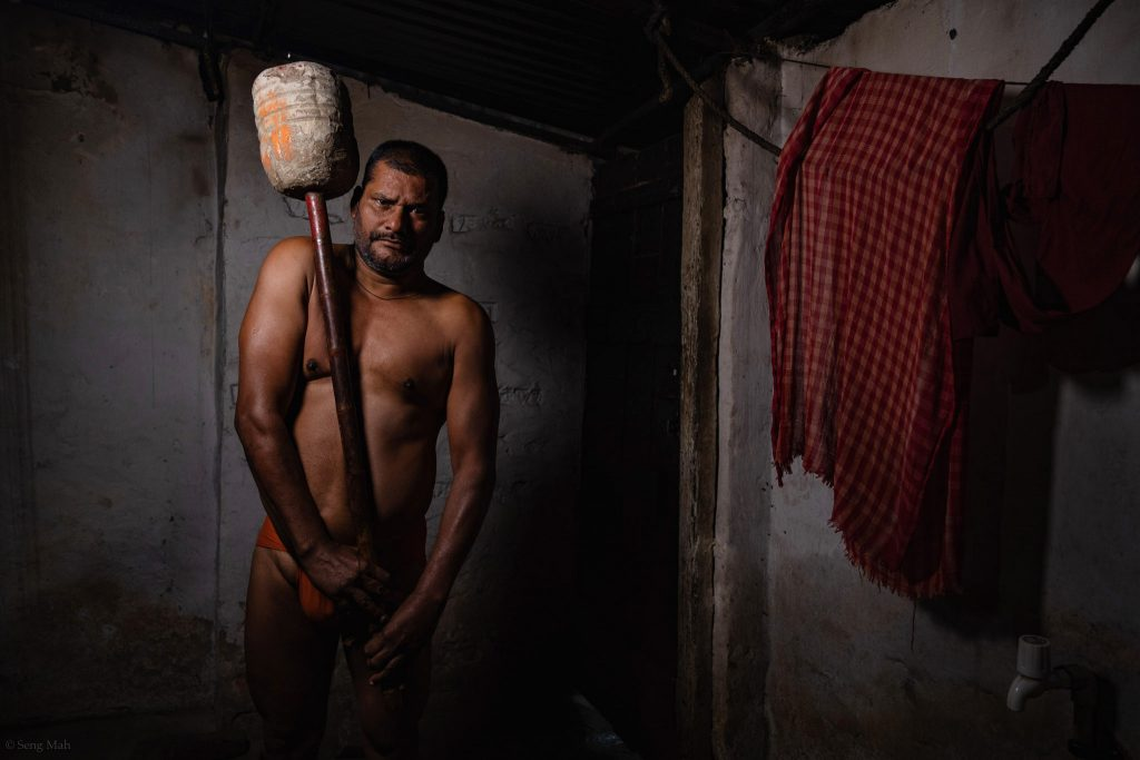 Wrestler, Ram Kumar Sharma, holding a gada (club) in the akhara in Kolkata.