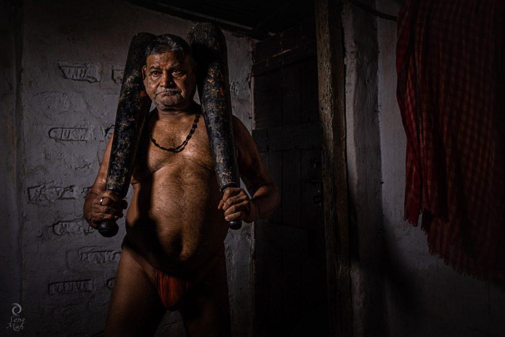 An elderly Indian wrestler wiedling two large metal clubs called mugdals.