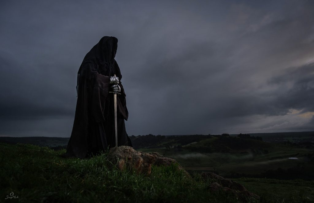 A man dressed as a Nazgul or Ring Wraith, completely covered in a hooded cloak and holding a sword, stands on a rock.