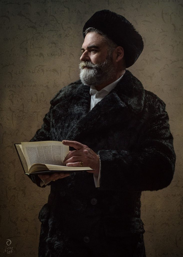 A bearded man, dressed in a thick faux fur coat and a Russian style hat, holding a book and looking into the distance.