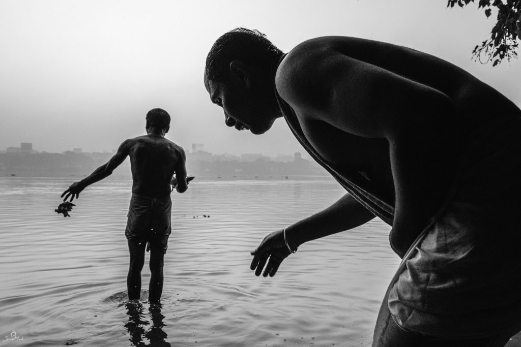 Black and white photo of morning bathers in Kolkata, India.