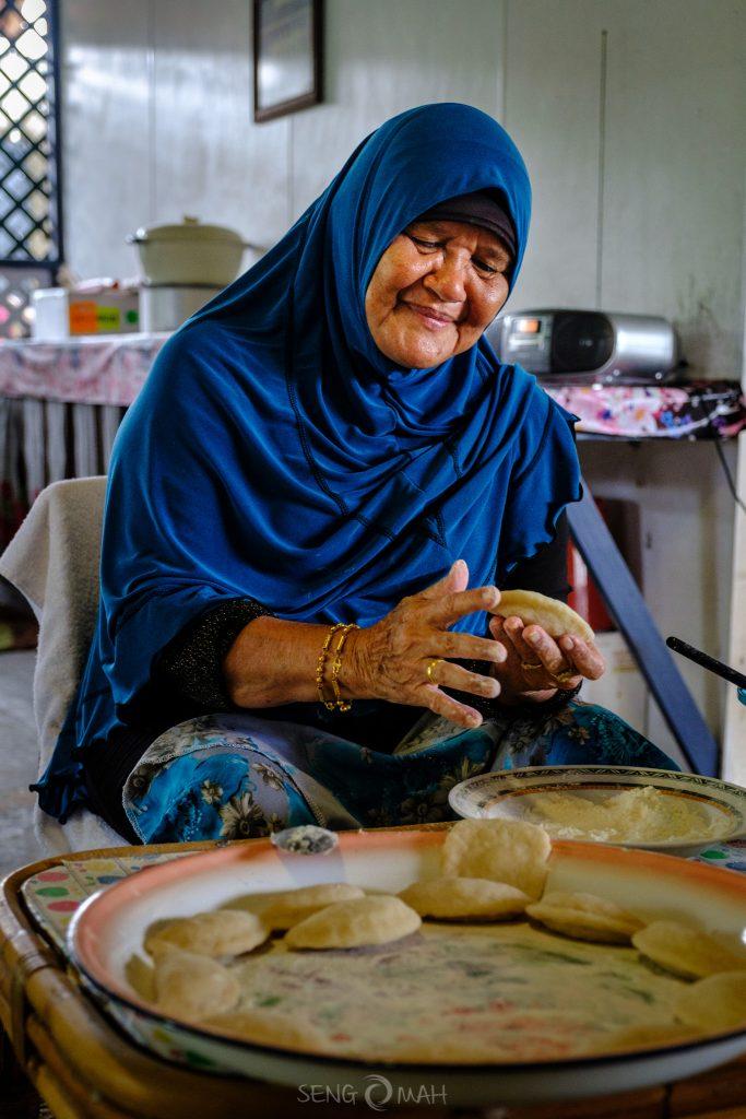 Nek Adillah making curry puffs